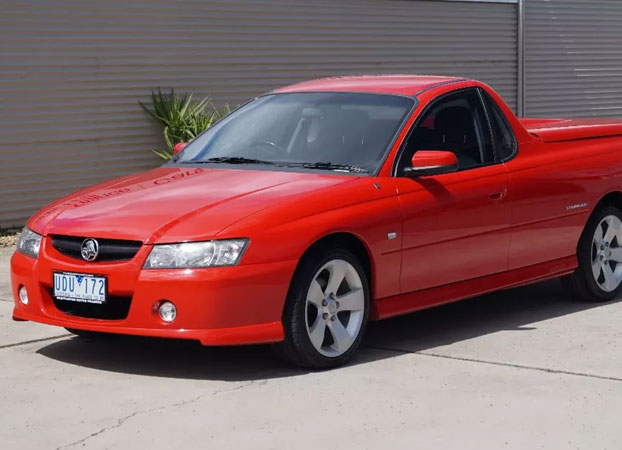 A red Holden car parked outside Shepparton Motor Traders dealership